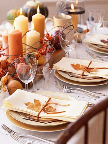 Autumn touches of bittersweet, leaves, and gourds grace this pretty Thanksgiving table. Start by arranging fall-color pillar candles on a wooden plank in the center of the table, then encircle them with gourds, berries, and vines. Let Mother Nature carry through to the place settings of golden yellow dishes by wrapping linen napkins in ribbon and dried leaves./