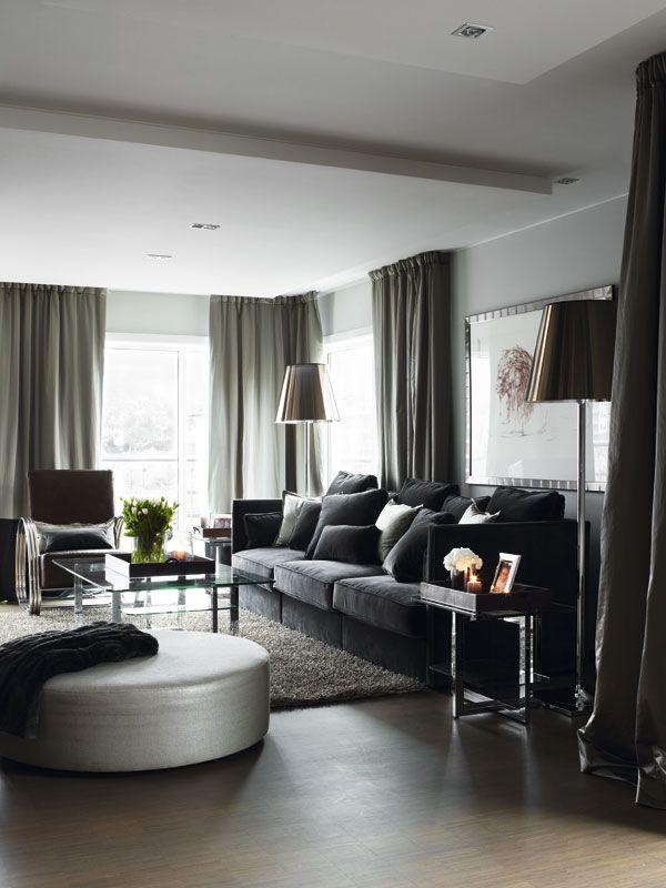 Her kan man slappe av foran peisen mens man gleder seg til å gå til bords. Myke, tepper og en herlig, komfortabel sofa som frister til å slå seg ned. Også her er det lange, rause silkegardiner med et avsluttende stykke med velur. (Sofa fra Gaston Y Danilea).