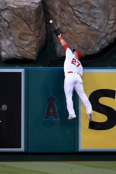 Mike Trout Photos - Mike Trout #27 of the Los Angeles Angels of Anaheim leaps unsuccessfully to catch this home run by Mike Moustakas #8 of the Kansas City Royals during the first inning of a baseball game between the Los Angeles Angels of Anaheim and the Kansas City Royals at Angel Stadium of Anaheim on April 26, 2016 in Anaheim, California. - Kansas City Royals v Los Angeles Angels of Anaheim