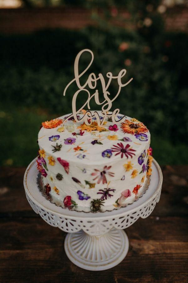 Completely beautiful wedding cake with edible wildflowers in the icing and a romantic white metal cake stand | Image by Suzy Goodrick Photography