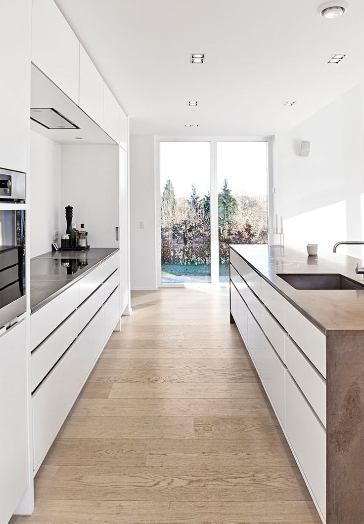 White and clean lines in the kitchen with white oiled oak as floor and special table top in Pietra di Fossena marble.