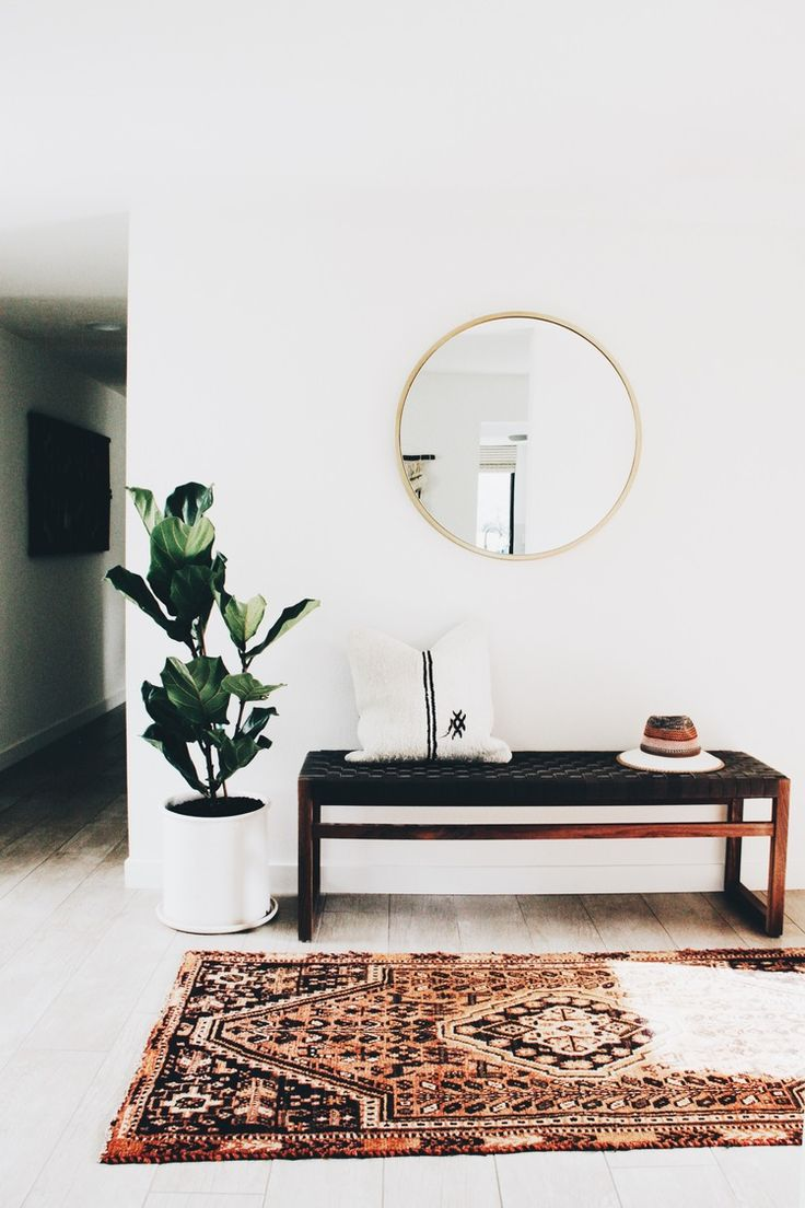 White wall. Entry way bench. Gold frame circle mirror. Fiddle leaf fig tree. Colorful patterned rug