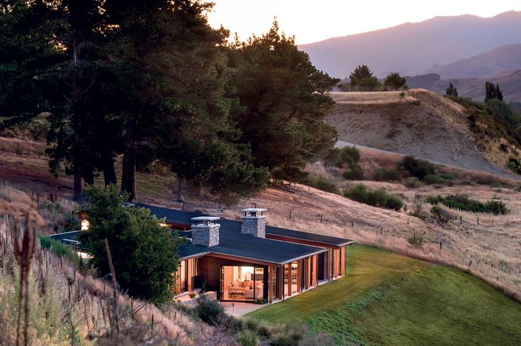 This holiday home near Wanaka, designed by Mason & Wales Architects, steps down the hillside over three levels, with a floating roof plane that follows the contour of the slope.