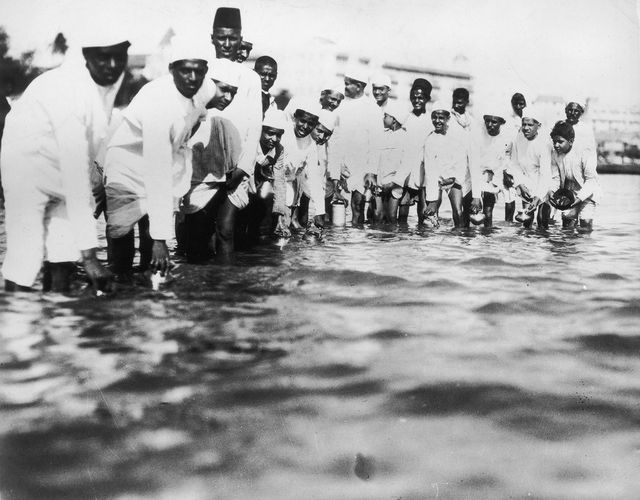 Gandhi's Historic March to the Sea in 1930: Followers of Gandhi fill plastic bottles with seawater during the Salt March of 1930 in India, to protest British colonial salt taxes.