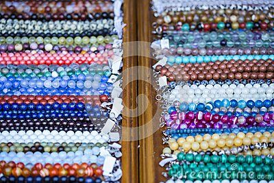 Close view of wooden shelf with aligned rows of colorful necklaces with price tags on the flea market. Shallow depth of field.
