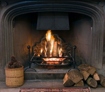 A roaring fire within a large stone arched fireplace, with pile of logs and basket of pine kernels in the foreground