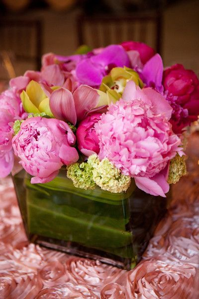lush tabletop arrangement of flowers in pinks and yellows