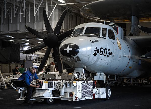 Aviation Boatswain's Mate (Handling) Airman Brian Rodrigues moves an E-2C Hawkeye, assigned to the Sunkings of Carrier Airborne Early Warning Squadron (VAW) 116, in the hangar bay of the aircraft carrier USS Theodore Roosevelt (CVN 71.