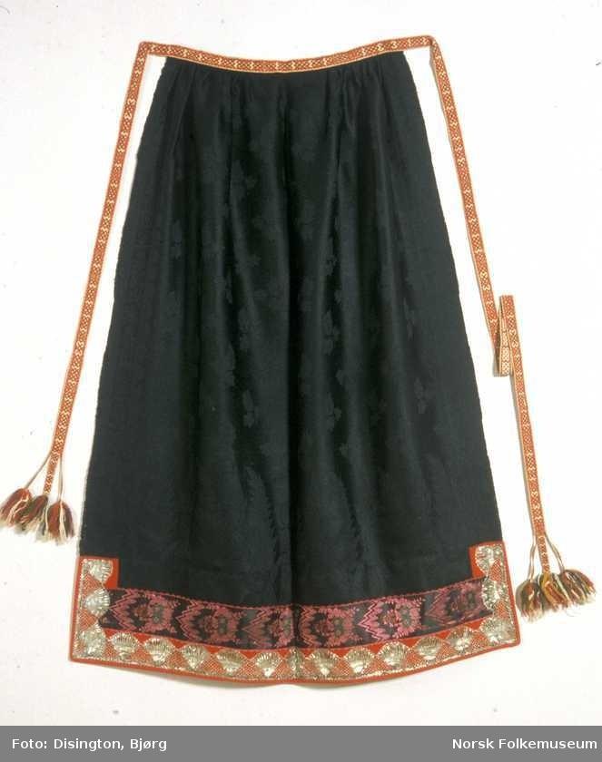 Digitalt Museum - Mulig en del av Astrid Bakkes brudedrakt,fra Tinn i Telemark, da hun giftet seg i 1864. Forkle i svart ulldamask, med grindvevde forklebånd.