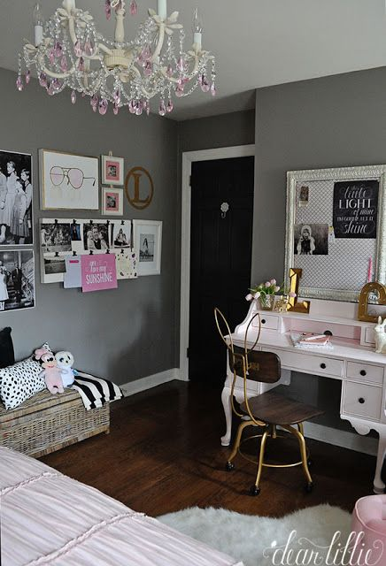 A pink chandelier and a gallery wall full of Sound of Music posters and family photos and drawings adds a fun touch in this pink, white, black and gray girls room. Fun artwork and a hanging clipboard from HomeGoods add finishing touches to the space. (sponsored pin)