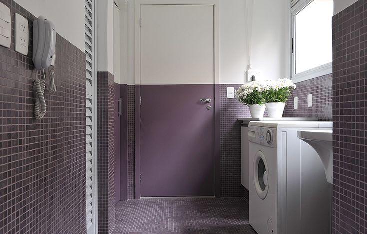 Moderna, a lavanderia recebeu pastilhas de vidro roxas no piso e na metade das paredes. Para dar continuidade, a porta é pintada com essa cor na mesma altura
