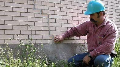 Une fissure dans la fondation se poursuit dans la brique et sous la ligne du sol