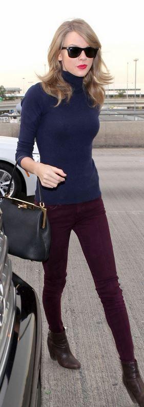 Who made  Taylor Swift's black handbag, brown boots, blue turtleneck sweater, and black handbag?