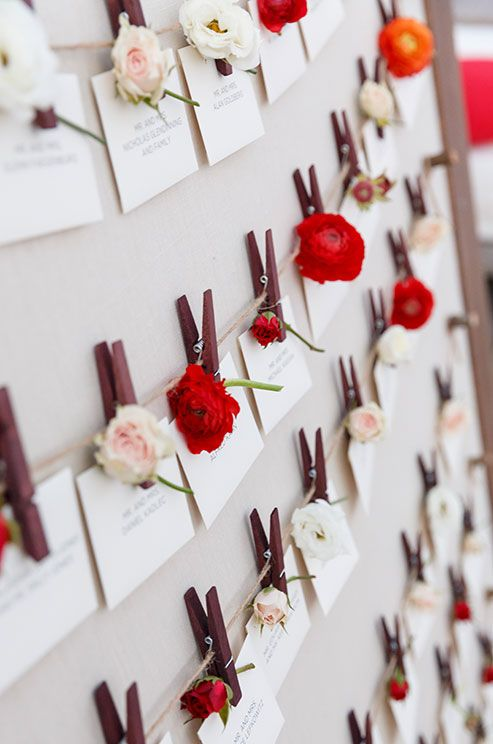 An escort card display is accented with fresh blooms of ranunculus and miniature roses.