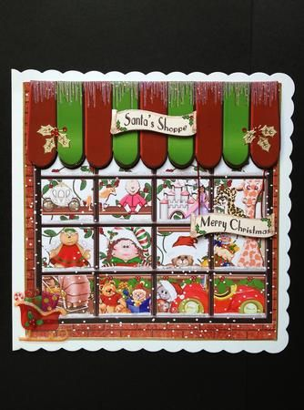 The Girl's Christmas Toy Shoppe on Craftsuprint designed by Barbara Alderson - made by SHELAGH E OSBORN WRIGHT - I printed the file on C.B's glossy paper and cut out the parts. I attached the shoppe front to an 8inch white scalloped card with DST. I edged 3 sides of the Toy shoppe with a plain gold border. I attached red shiny thread to the back of the Merry Christmas banner and added mini foam pads, leaving the back covered to make a hanging sign. I glued the thread ends with DST to the top…
