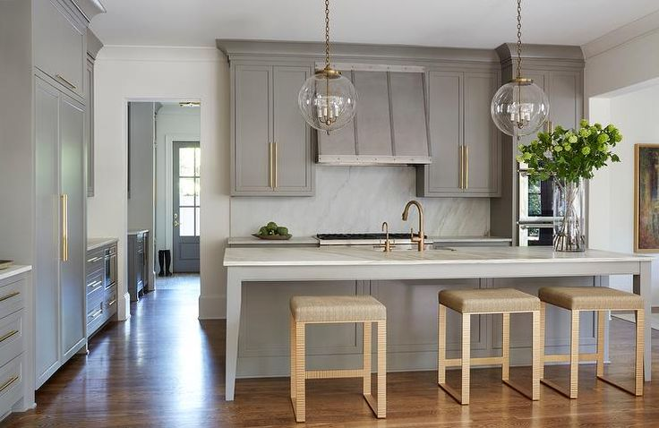 Gold and gray kitchen features creamy gray cabinets adorned with long brushed brass pulls paired with white marble countertops and backsplash.