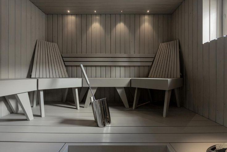 Moderni sauna on värjätty tyylikkään harmaaksi. Lauteiden tilalla on komeat penkit ja kaunis valaistus antaa saunalle viimeisen silauksen.