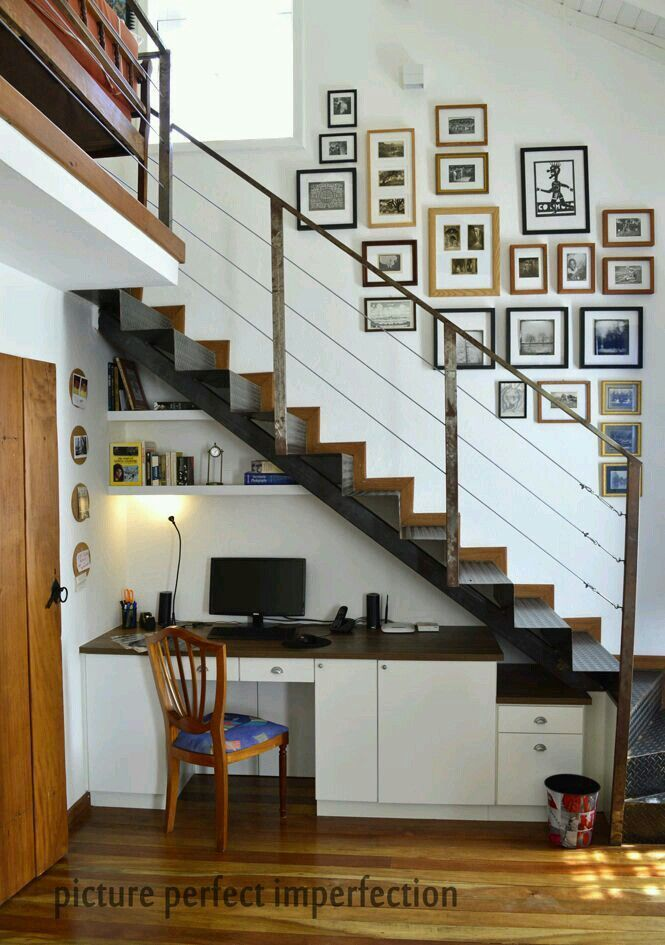 Local craftsmen executed our design for a custom-fitted office under the  stairs leading to the mezzanine.