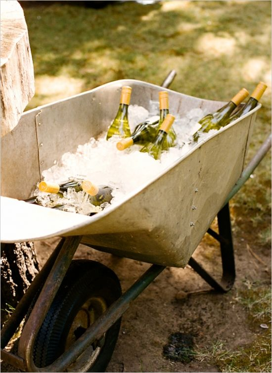 Just some wine bottles chilling in a wheelbarrow