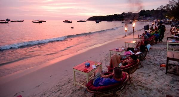 Sihanoukville, Cambodia, vacationers can watch the sun set over Ochheuteal Beach, as they sip cocktails and await nightfall by the light of tiki torches