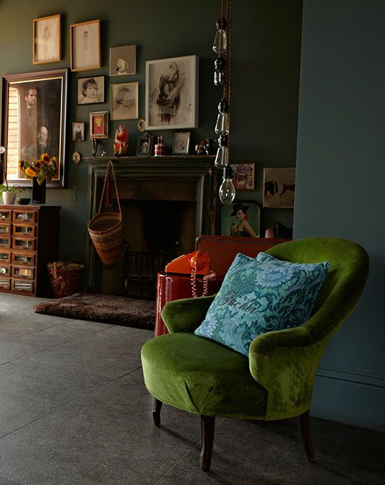 Olive green velvet chair against moody teal wall
