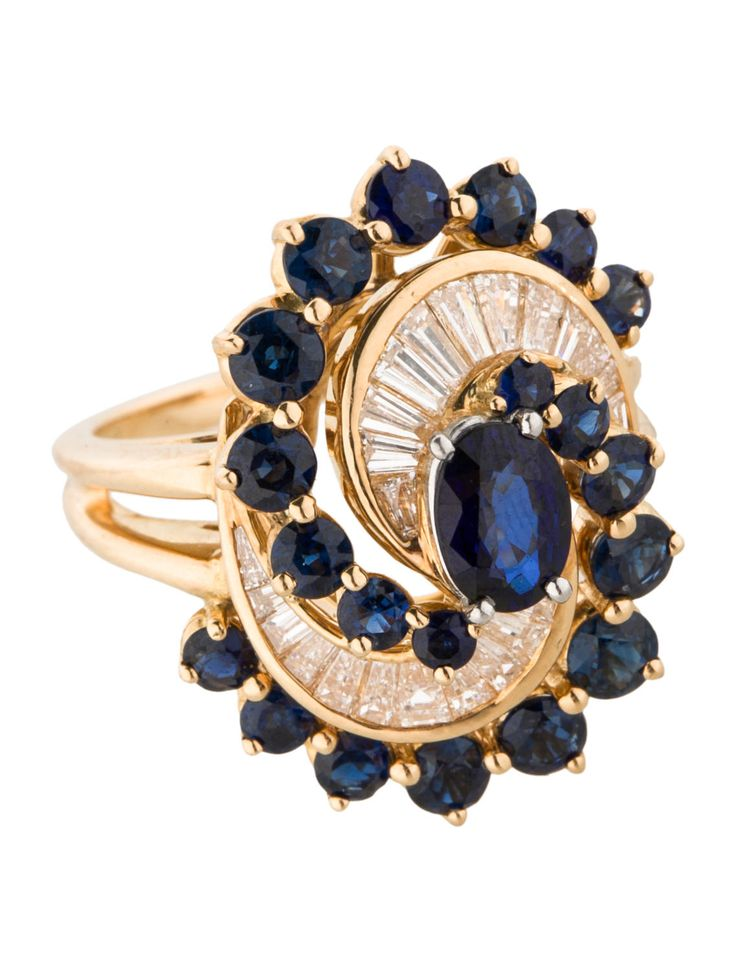18K yellow gold Oscar Heyman swirl ring with platinum prong set faceted oval blue sapphire at center, channel set baguette diamond embellishments and prong set blue sapphire accents. Ring size 6.