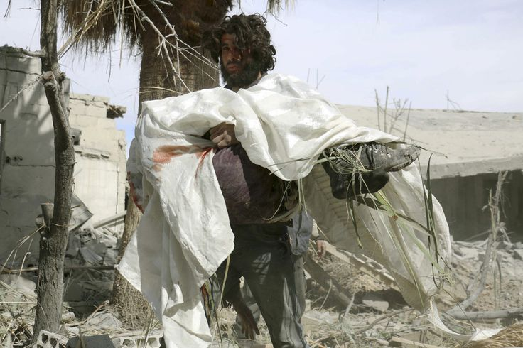 A man carries the body of his mother after what activists said were air strikes by forces loyal to Syria's President Bashar al-Assad in Marj Al Sultan, in the eastern Damascus suburb of Ghouta on February 27, 2015.