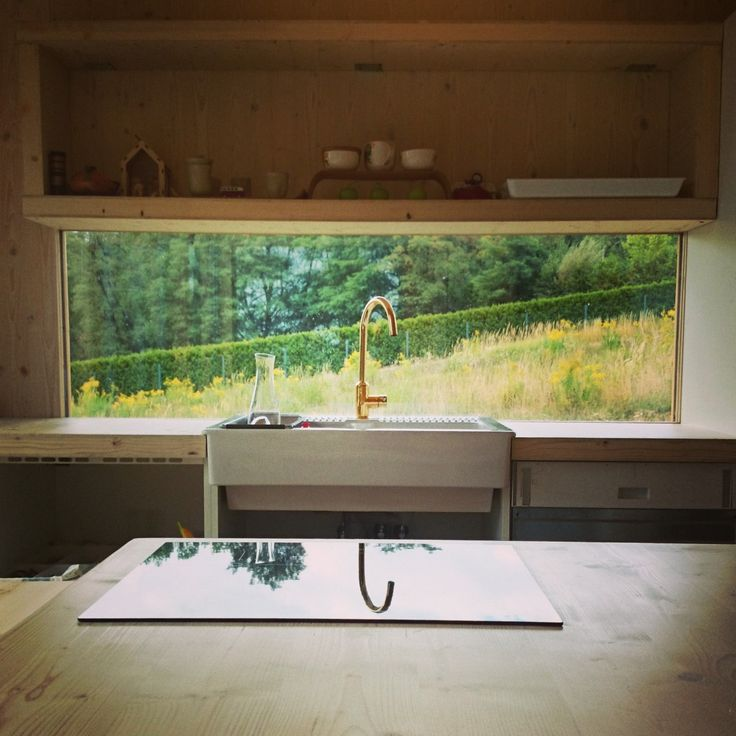 Mycie naczyń z widokiem na łąkę. Zestawy szklane, bez ram okiennych bezpośrednio zamontowane do ściany to sprytne i tanie rozwiązanie.