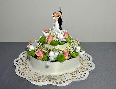 Splendida torta nuziale a due piani realizzata con rose e nastri in raso bianco