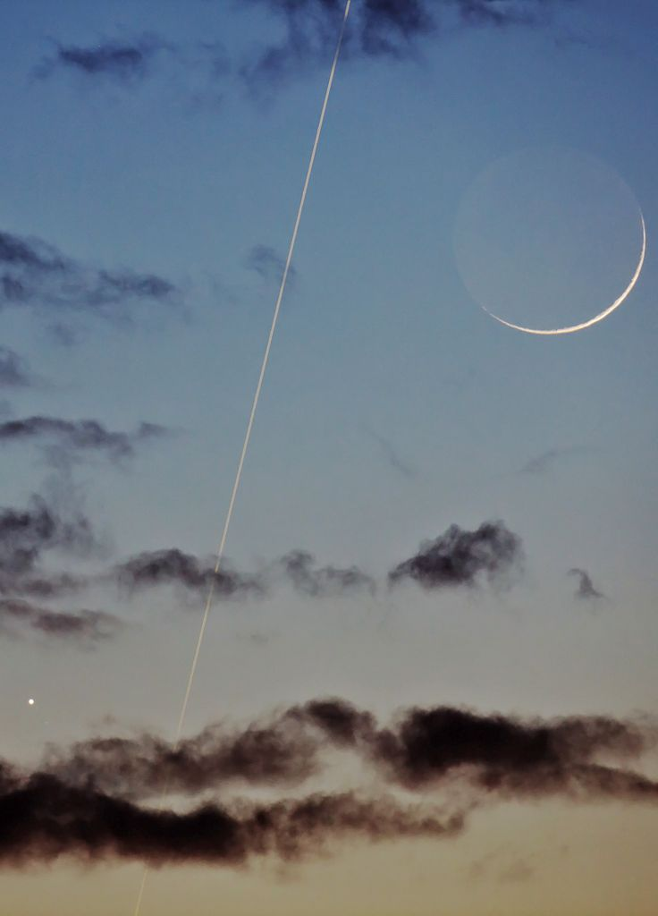 Earth's moon 1.5 days after the New Moon; with the International Space Station seen streaking across the sky and Jupiter shining amid the clouds.
