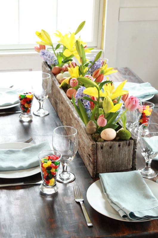 Easter tablescape - Glasses filled with jelly beans, a rustic wooden box filled with vases of spring flowers (vases are covered by moss) and colored eggs, and pastel napkins on pale plates. Perfect.