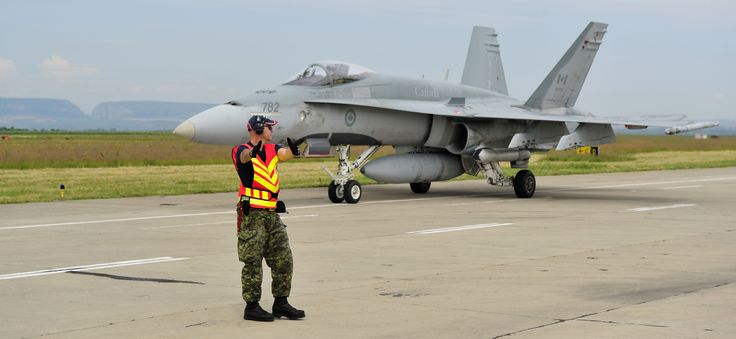 Tail Number (782): Corporal Dan Van Haaren marshalls in a CF-18 Hornet on 5 June 2014 in Câmpia Turzii, Romania where members of Canadian Air Task Force are participating in NATO Reassurance Measures.   Photo by LS Alex Roy, 3 Wing Imaging (BN2014-1018-04)