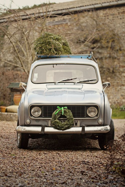 Vintage car with Christmas tree on top and wreath on the front.
