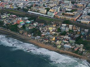 La Perla is a slum in Puerto Rico, home to about 340 people.  It is separated by a wall from the city of San Juan. Beautiful from afar, but sad up close. The streets of La Perla are not indicated on most city maps in order to deter tourists from walking into the high crime area.