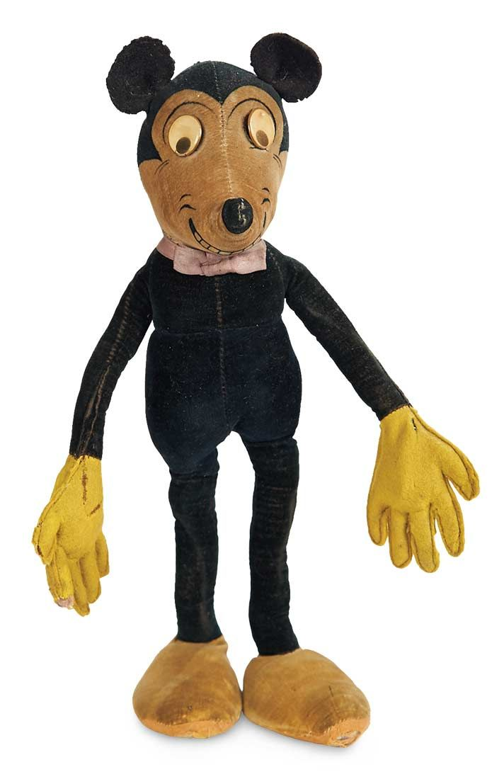 "English velvet Mickey Mouse by Dean's Rag, circa 1930. 13"" (33 cm.) standing slender-bodied Mickey Mouse has celluloid disc flirty eyes,painted mouth with teeth, large velvet shoes, felt hands and feet. From Theriault's Antique Doll Auctions."