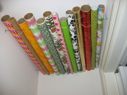 What a great way to take advantage of empty space! Use the ceiling of a closet to store those pesky wrapping paper rolls that always get crumpled and lost in the closet. You could also do this on the side of a closet to keep them standing upright and out of the way.