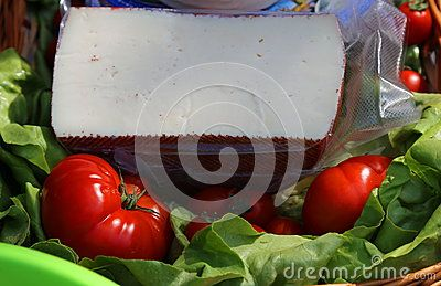 Cheese on green salad and tomatoes - piece of cut cheese.