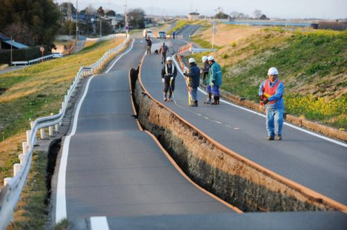 Workers inspect a caved-in section of a prefectural road in Satte, Saitama Prefecture, after one of the largest earthquakes ever recorded in Japan slammed its eastern coast 11 March 2011