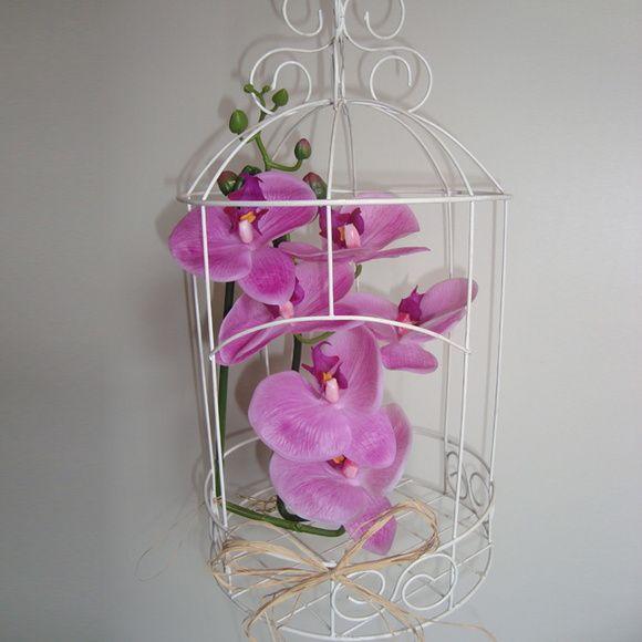 Numa delicada gaiola de metal branca colocamos uma orquídea de silicone rosa, muito similar a flor natural para decorar. Uma peça linda para decorar sua casa (varanda, sala e quarto) ou mesmo deixar sua festa (infantil, casamento, bodas, quinze anos, noivado) personalizada, principalmente se a mesma seguir a temática provençal. Você poderá acomodá-la na mesa central, no chão próximo a mesa, em aparadores próximo dos bem-casados. Use a imaginação!    Medidas da gaiola: 22 x 40 x 22 - (larg x…