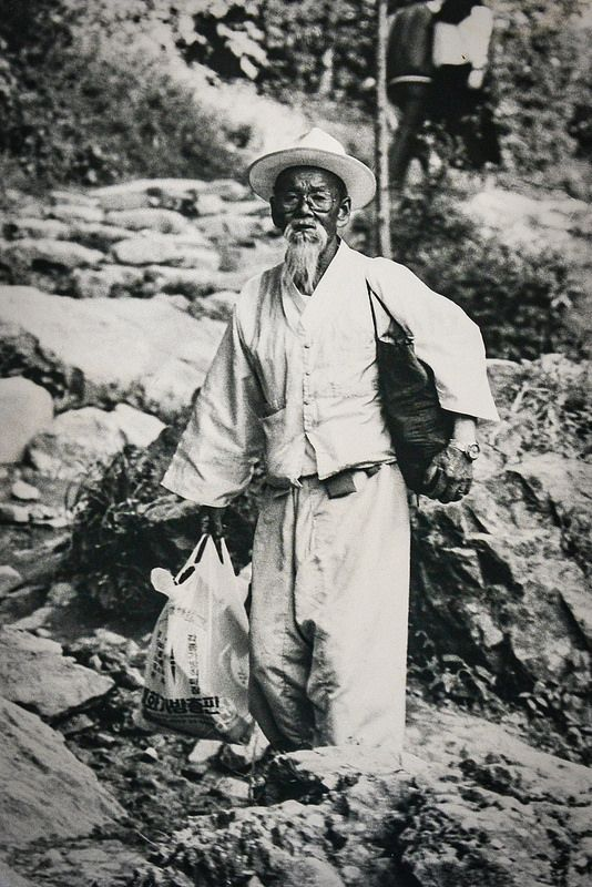 """Haraboji"" (Grandfather) was taken in the Summer of 1986 on Muedeung Mountain, outside Gwangju City, South Korea, by Silverback on Flickr. ""This image has occasionally played though my mind over the years as representative of the rapid change going on in this great nation. …Some of these ideas are shown here with the combination of traditional wardrobe with modern eyeglasses, wrist watch, and plastic bag."""