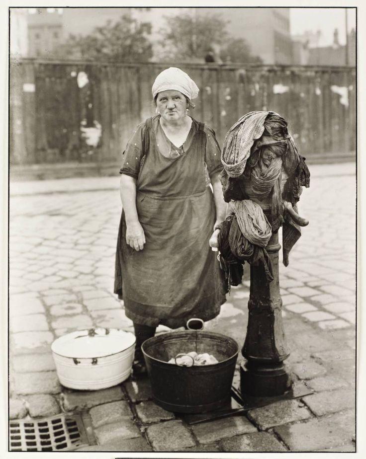 """Nesta foto podemos ver uma mulher com idade compreendida entre os 45 e os 50 anos. Posemos concluir que esta senhora é uma """"lavadeira"""" devido a vários factores desde a contida de de roupa que tem ao seu lado esquerdo as bacias que estão cheias de roupa a beira dos seus pés. usa uma espécie de lenço na cabeça e um avental."""