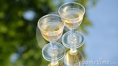 Glitter wine glasses on a mirrored sky abstract blurred background, food and beverages composition.