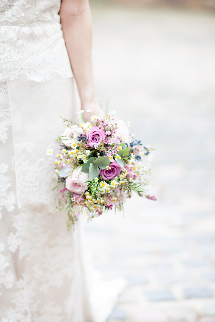 This wild and textural bouquet is filled with eucalyptus, feverfew daisies, wax flowers, viburnum berries, memory lane roses, cool water roses and rosemary. The photograph is by Light & Lace Photography.