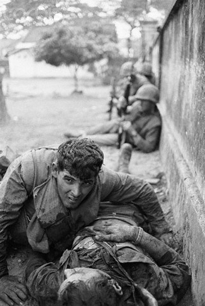 Feb 1968, Hue, South Vietnam --- A young marine tries to help a wounded friend during an assault at the 'Citadel Wall' in Hue, Vietnam during the Vietnam War. Image by © Bettmann/CORBIS ~ Vietnam War