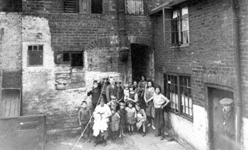 Family gathering at the door of slum 'court' in Sheffield, 19th century