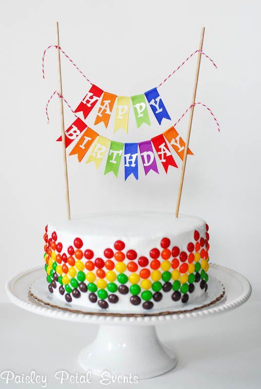 Torta circular en doble altura cubierta con fondant blanco y decorada lateralmente con circulos de colores y banner en la parte superior  con leyenda.