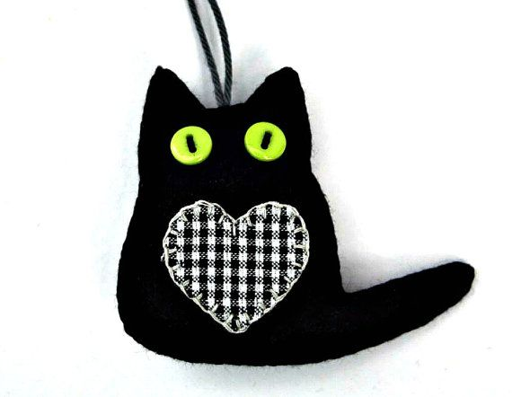 Set of three little black felt cats with appliqued fabric heart and button eyes. They are lightly padded, with blanket-stitched edges. Each cat