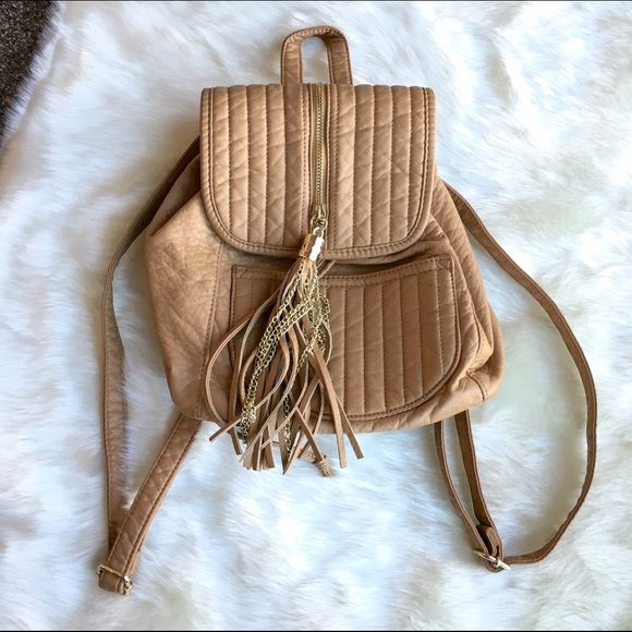 """Nude Backpack Adorable backpack with tassels. Nude color. Small pocket inside as well as outside. Clean, Smoke Free Home.  All Sales Final.  Fast Ship! Thanks! Check out my other items!                                                ✨✨✨✨✨15% off bundles✨✨✨✨  **NO TRADES or HOLDS PLZ** **will not reply to """"lowest""""** Bags Backpacks"""