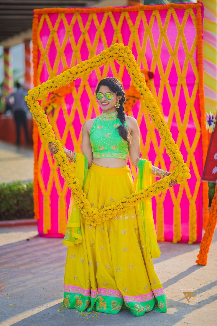 When a bride as cool and as fun as Teju is planning her Mehendi, we must feature the grand fun-o-holic event!  The stunning bride doesn't overload herself with loads of jewels; instead, she keeps it chic and simple with dangling earrings, glittering bangles and a pair of swaggy aviators. To add to her cuteness, lovability and charm the funny photo booth props are doing just the trick.  The decor and theme are inspired by the new-age funky touch, it features g...