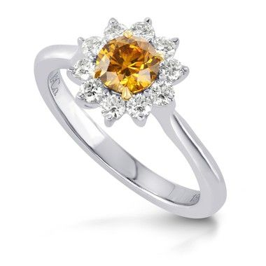 This Deep Brownish Yellowish Orange Round Brilliant Diamond Ring has a depth and intensity that is hard to come by. The surrounding White Diamonds are set in a filigree work forming a petal formation around the beautiful centerpiece.